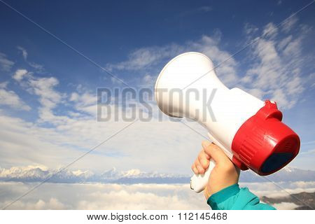 one hand hold loudspeaker against the sky
