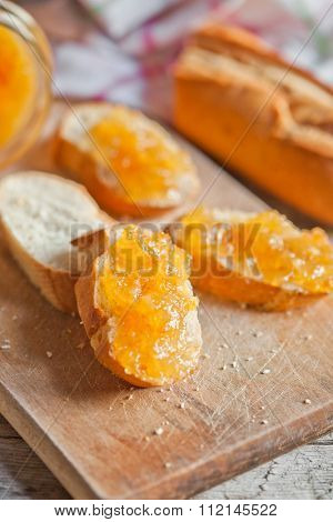 fresh bread with orange jam on background wooden plank