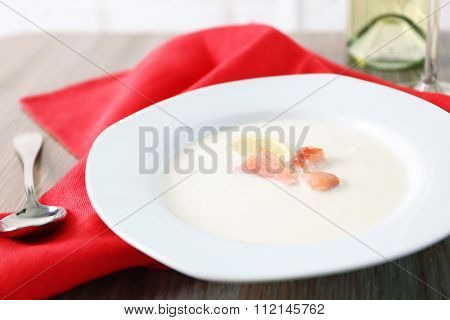 Tasty salmon cream soup with wine and red cotton serviette on wooden table, close up