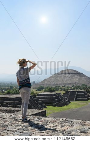 Young Woman On Top Of Pyramid Covering Her Eyes From Sun Overlooks Ruins Of Teotihuacan