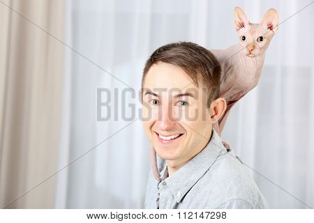 Young handsome man holding a cat on light tulle background