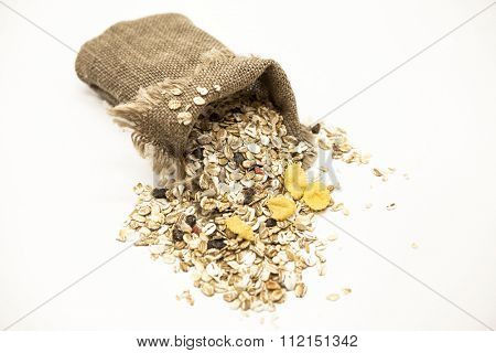 Healthy eating oat flakes in a linen sack, closeup on a white background.