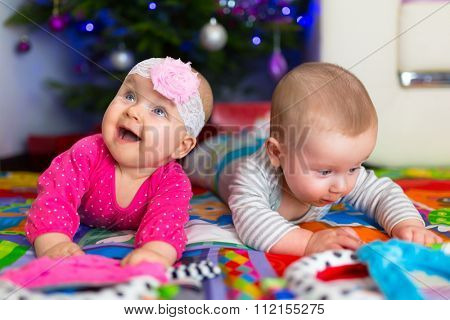 Babies with presents under Christmas tree