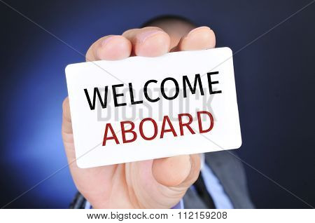 a young caucasian businessman shows a signboard with the text welcome aboard