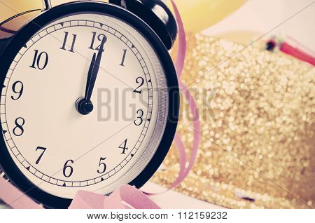 closeup of a watch at twelve, balloons, a golden top hat, streamers and confetti for the new years party, with a filter effect
