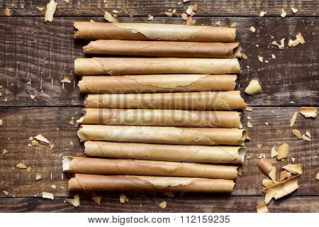 some homemade neulas, typical thin biscuit rolls eaten in Christmas in Catalonia, Spain, on a rustic wooden surface