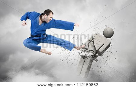 Young determined karate man breaking with leg concrete figure