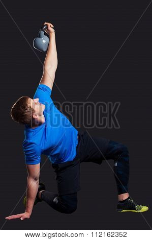Portrait of a man standing with kettlebells on black background