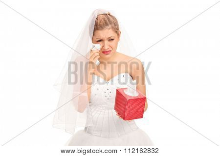 Young bride in a wedding dress crying and wiping her tears isolated on white background