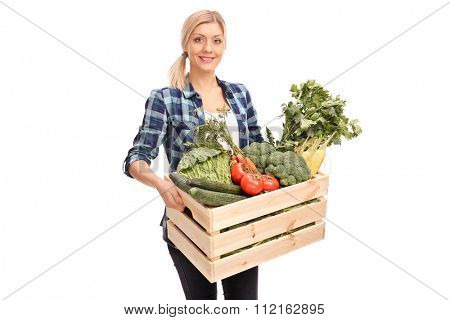 Female agricultural worker carrying a wooden crate full of fresh vegetables isolated on white background