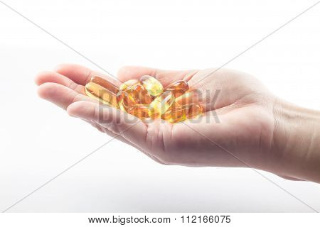 Hand Holding Fish Oil Capsules On White Background