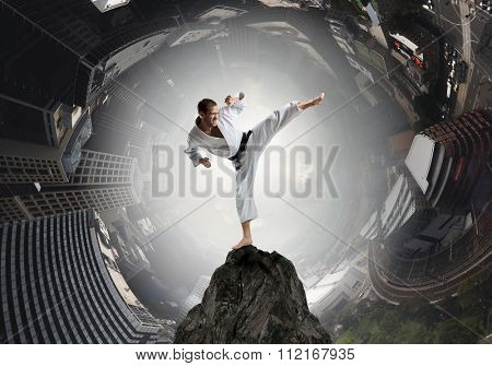 Young determined karate man on top high in sky