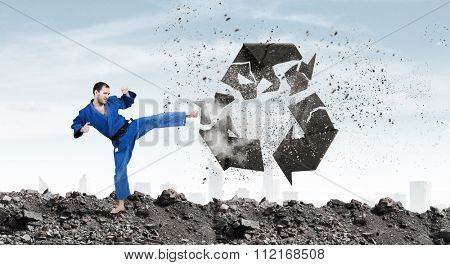Young determined karate man breaking with leg concrete recycle sign