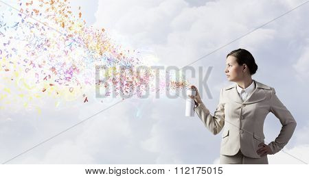 Young businesswoman spraying characters from aerosol