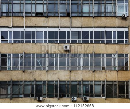 dirty old facade with windows of factory,