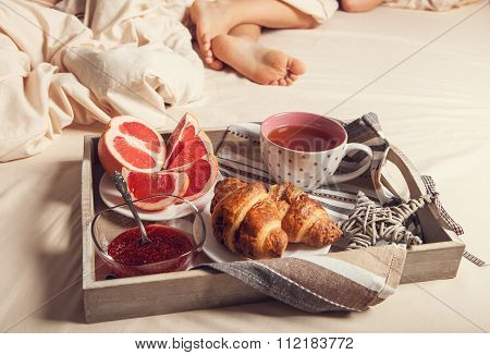Breakfast With Croissant On Service Tray On The Bed Near Sleeping