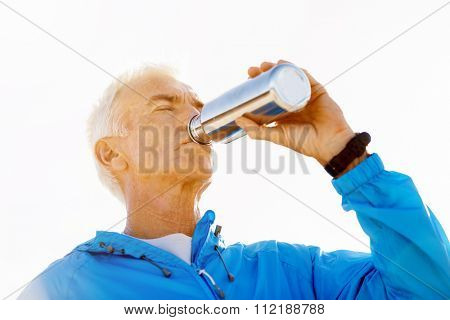 Young man in sport wear drinking from sports bottle