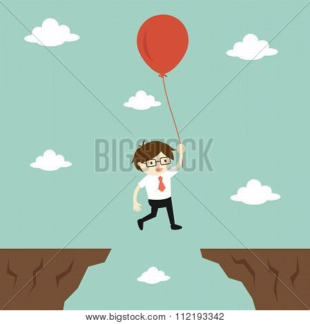 Business concept, businessman flies across a gap to another cliff by using balloon.