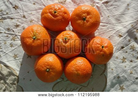 Some ripe mandarin fruit on wooden background