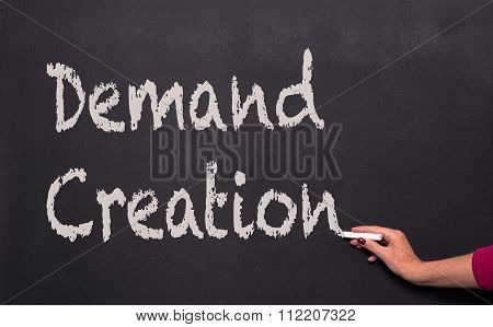 Woman's Hand With Chalk On Blackboard Writing, Demand Creation