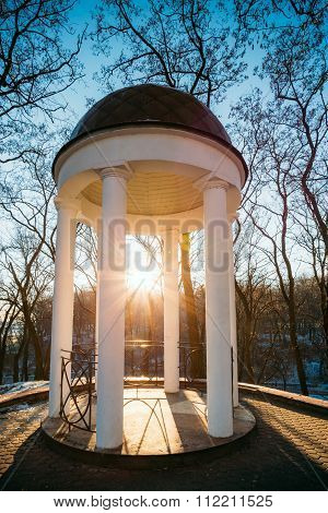 Sun at sunset shining through gazebo in city park in Gomel, Bela
