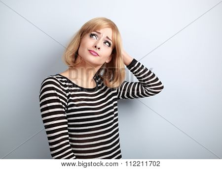 Disappointed Young Blond Woman Scratching The Head And Looking Up