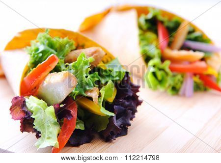 Healthy chicken strips and fresh salad wrapped in a corn tortilla