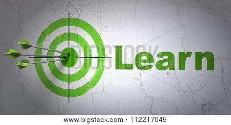 Education concept: target and Learn on wall background