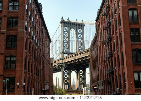 George Washington Bridge as seen from Street Level Between Low Rise Apartment Buildings with Traditional Architecture and View of New York City Skyscrapers in Background, New York, USA