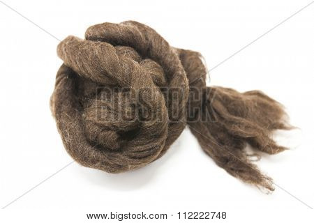 Brown piece of Australian sheep wool Merino breed close-up on a white background.