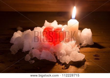 Heart From Red Ice On White Snow And The Candle Burning With A Row