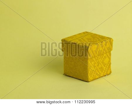 closed yellow gift box on the yellow background