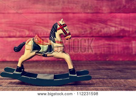 an old wooden rocking horse on a rustic wooden surface