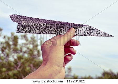closeup of the hand of a young caucasian man about to throw a paper plane made with a printed paper with non-sense words, outdoors