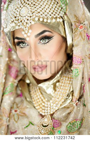 Traditional ethnic bride in costume with heavy jewellery and hijab