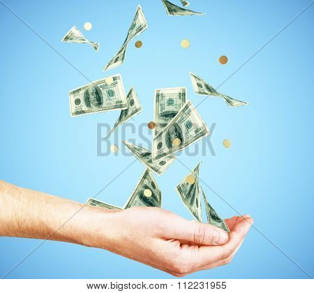 Human Hand With Money And Coins Falling At Blue Background