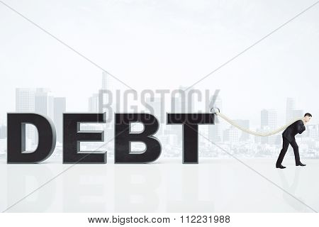 Debt Burden Concept With Businessman Pulls Debt Word On The Rope At City Backgroound