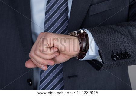 Young Business Man Looking At His Wristwatch Checking The Time