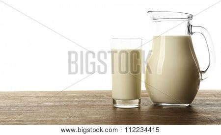 Milk in glass and in jar on table isolated on white background
