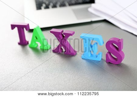 Alphabet TAXES and laptop on table