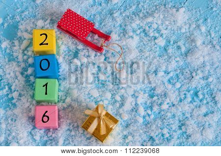 New 2016 Year wood number on color wooden cubes with snow, sled, gift and empty space for text. Happ