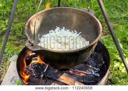 Large Pot Over A Campfire Cooking In Cast-iron Cauldron In Nature. Food, Camping, Cooking Onion Over