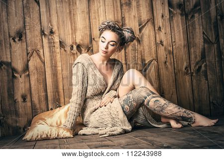 Beautiful young woman with dreadlocks hairstyle posing over wooden wall. Beauty, fashion. Hairstyle. Make-up.