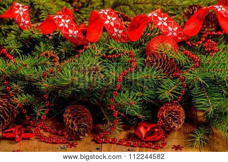 Festive Christmas Background - fir branches with red baubles and fir cones.