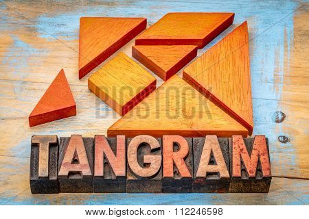 seven tangram wooden pieces, a traditional Chinese puzzle game with tangram word spelled in vintage letterpress wood type