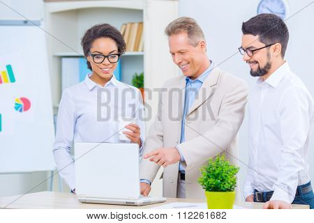 Three office workers discussing a project.