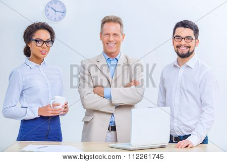 Three office colleagues are posing on the camera.