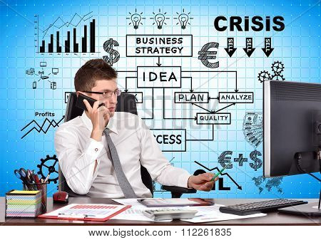 Businessman Sitting In Office With Phone