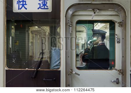 TOKYO JAPAN - NOVEMBER 16 2015: An unidentified Japanese train conductor announce the schedule for boarding commuters on a Tobu - Nikko train at Asakusa station