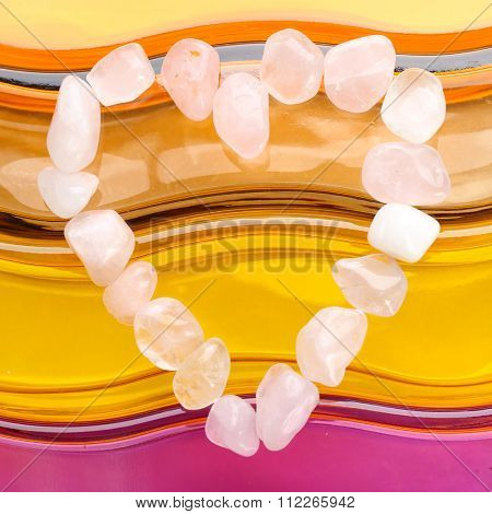 Heart shaped composition of semiprecious stones on bright background